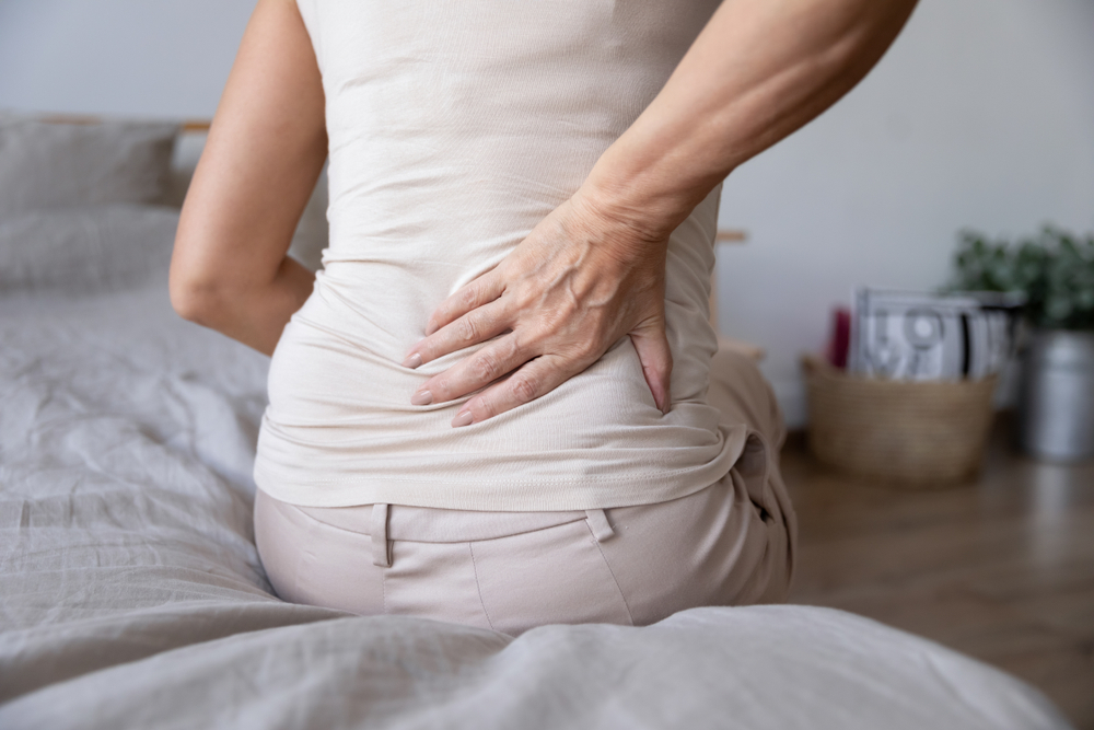 mature woman suffering from lower spine pain sitting on bed